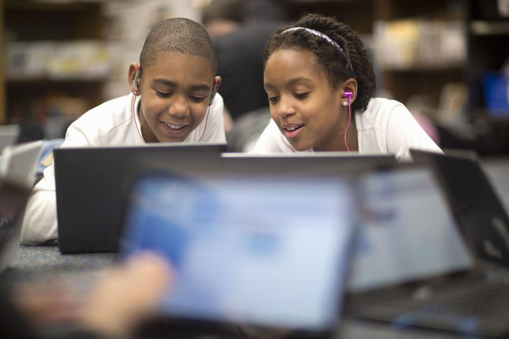 Two elementary students share a laptop in a classroom